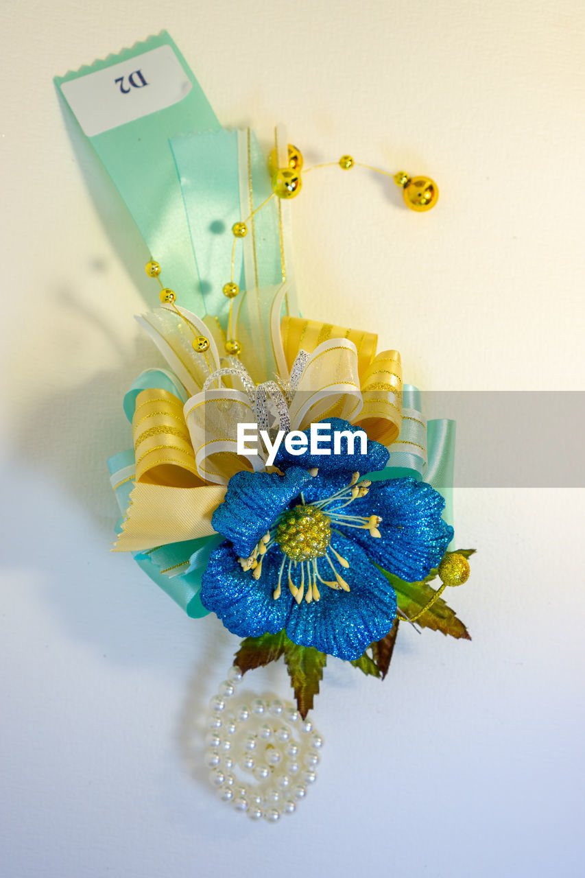 blue, indoors, studio shot, flowering plant, flower, no people, close-up, plant, still life, high angle view, white background, nature, decoration, yellow, single object, artificial, freshness, creativity, art and craft, vase, luxury
