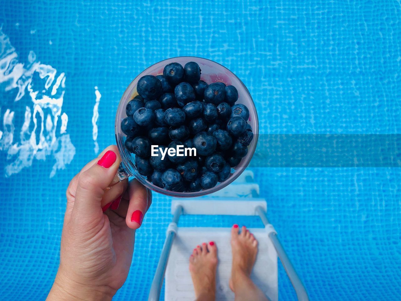High angle view of woman holding blueberries over the pool