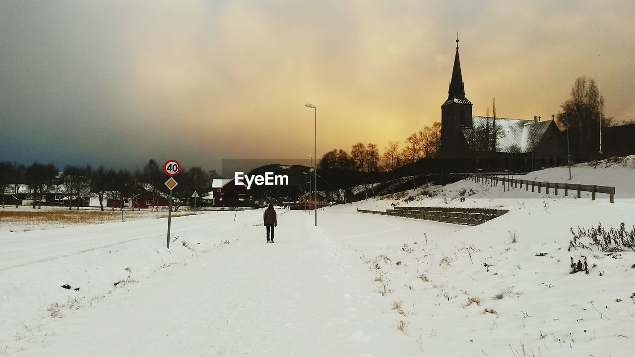 Rear view of man standing on snow covered field by church against sky during sunset