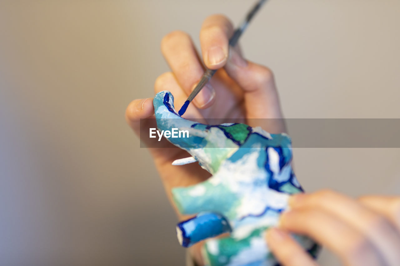 Cropped hand of person painting decoration