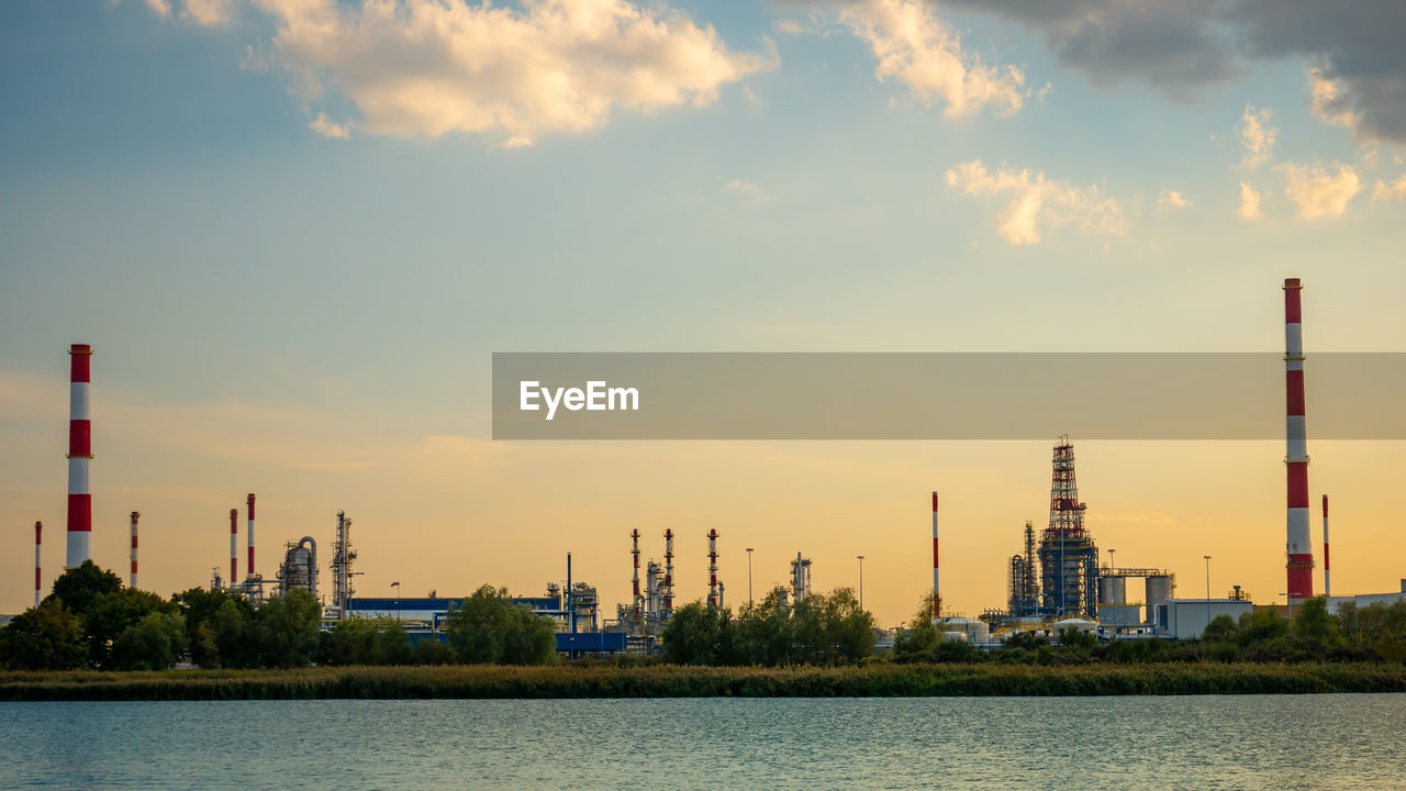 industry, factory, building exterior, architecture, sky, built structure, water, nature, smoke stack, waterfront, sunset, cloud - sky, no people, outdoors, tower, tall - high, river, orange color, fuel and power generation, skyscraper, pollution