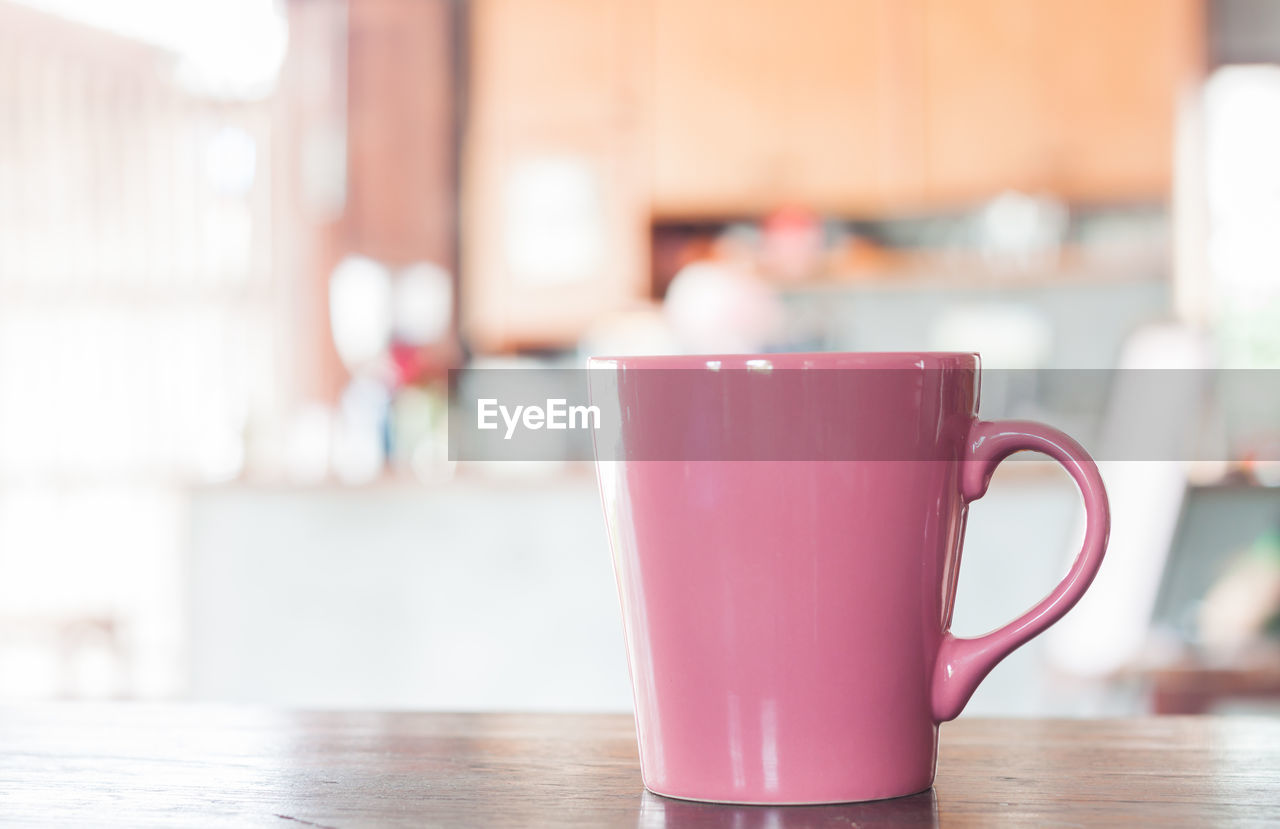 table, cup, indoors, drink, focus on foreground, mug, close-up, pink color, still life, refreshment, food and drink, coffee cup, wood - material, no people, day, freshness, home interior, red, hot drink, tea cup