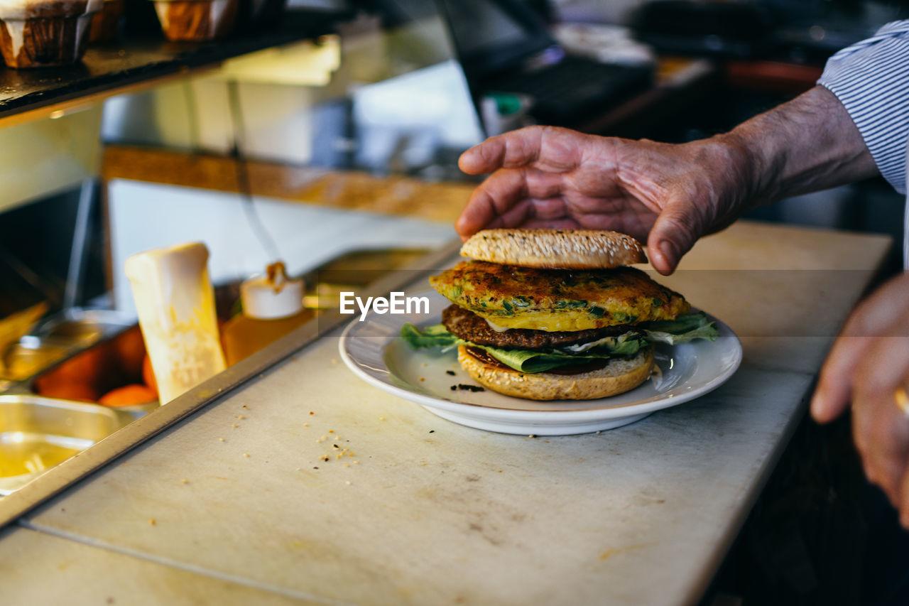 Midsection of man preparing burger in restaurant
