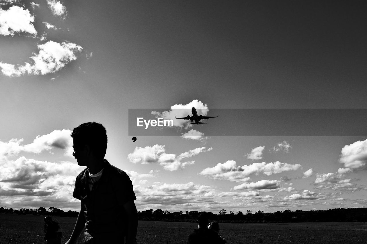 Playful boy on field against airplane flying in sky