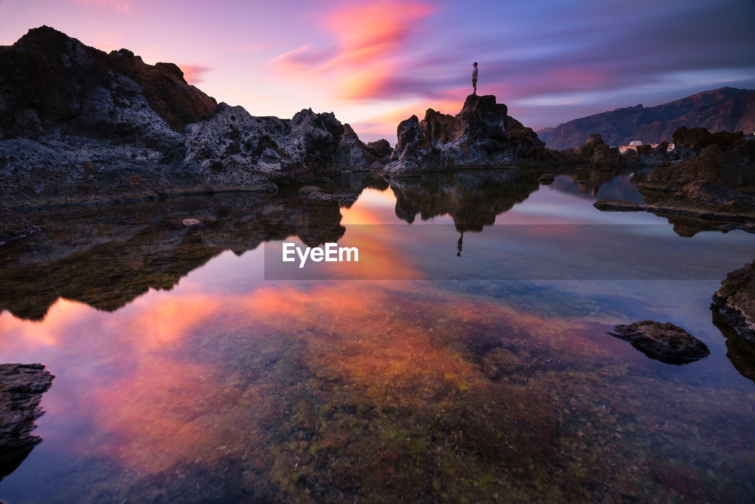 Scenic view of lake by rock formation against sky during sunset