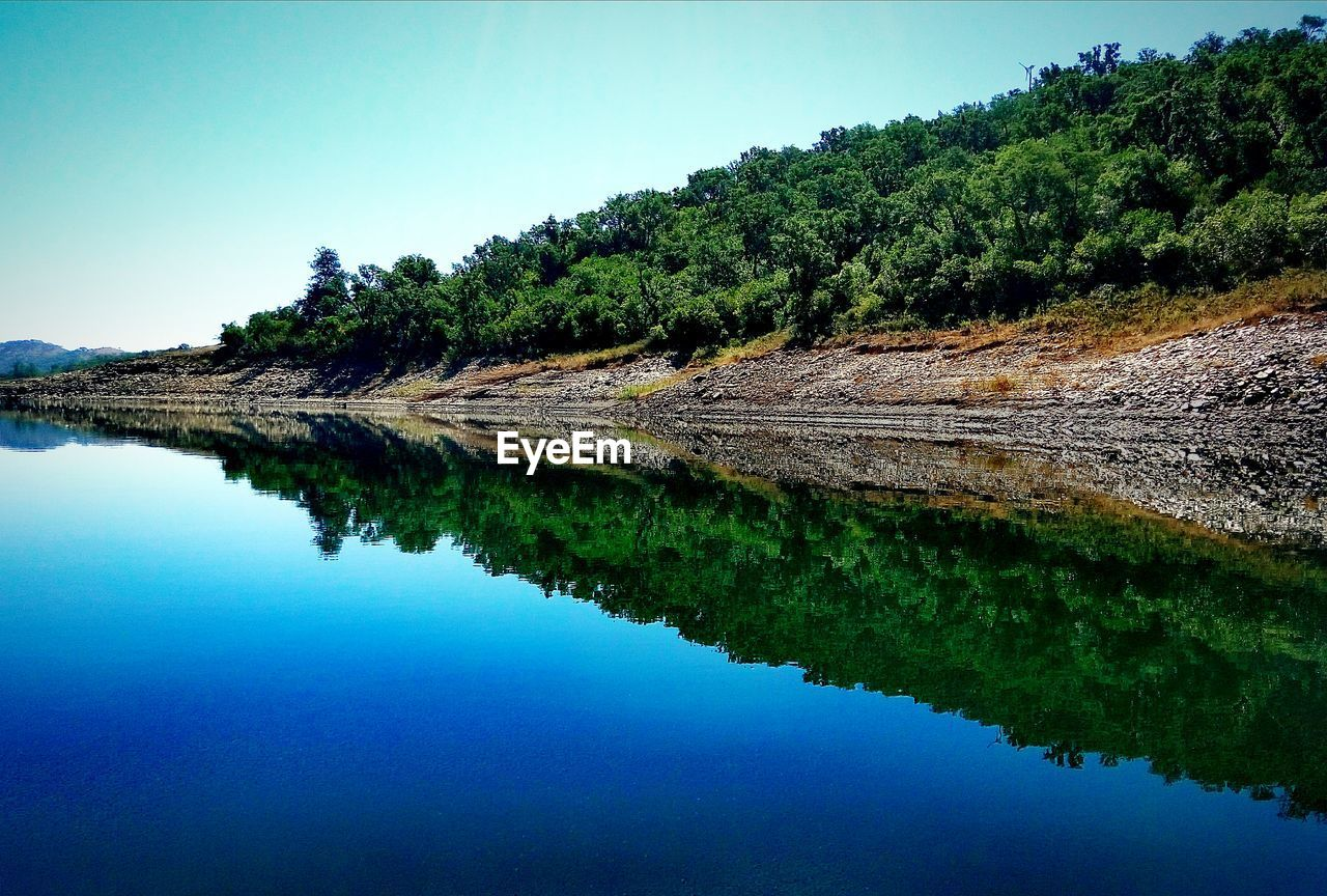water, reflection, nature, tranquil scene, beauty in nature, scenics, tranquility, outdoors, lake, tree, no people, standing water, blue, day, sky, waterfront, green color, mountain, landscape, growth, clear sky, grass