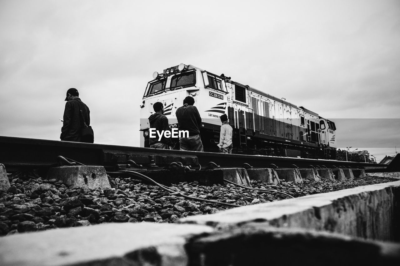 Locomotive On Railroad Track Against Cloudy Sky