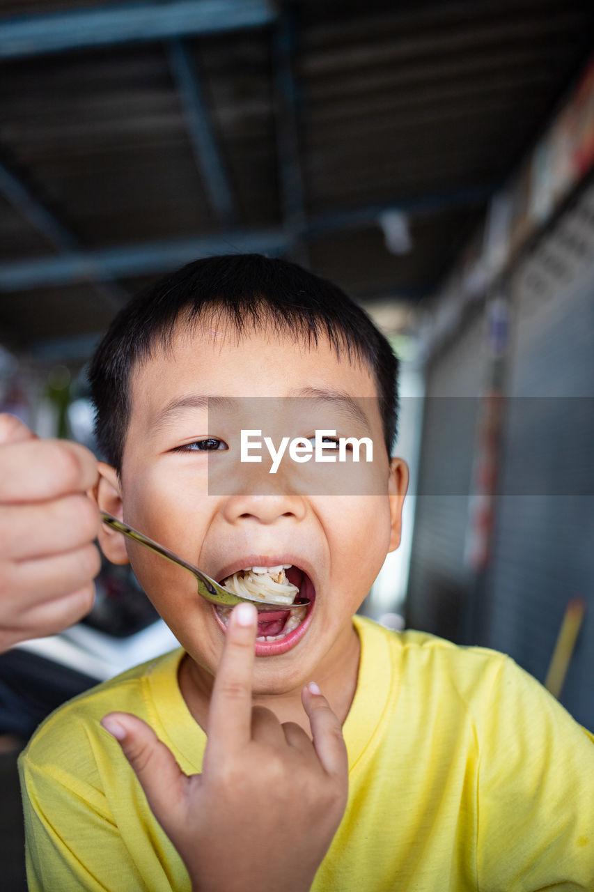 PORTRAIT OF BOY EATING ICE CREAM