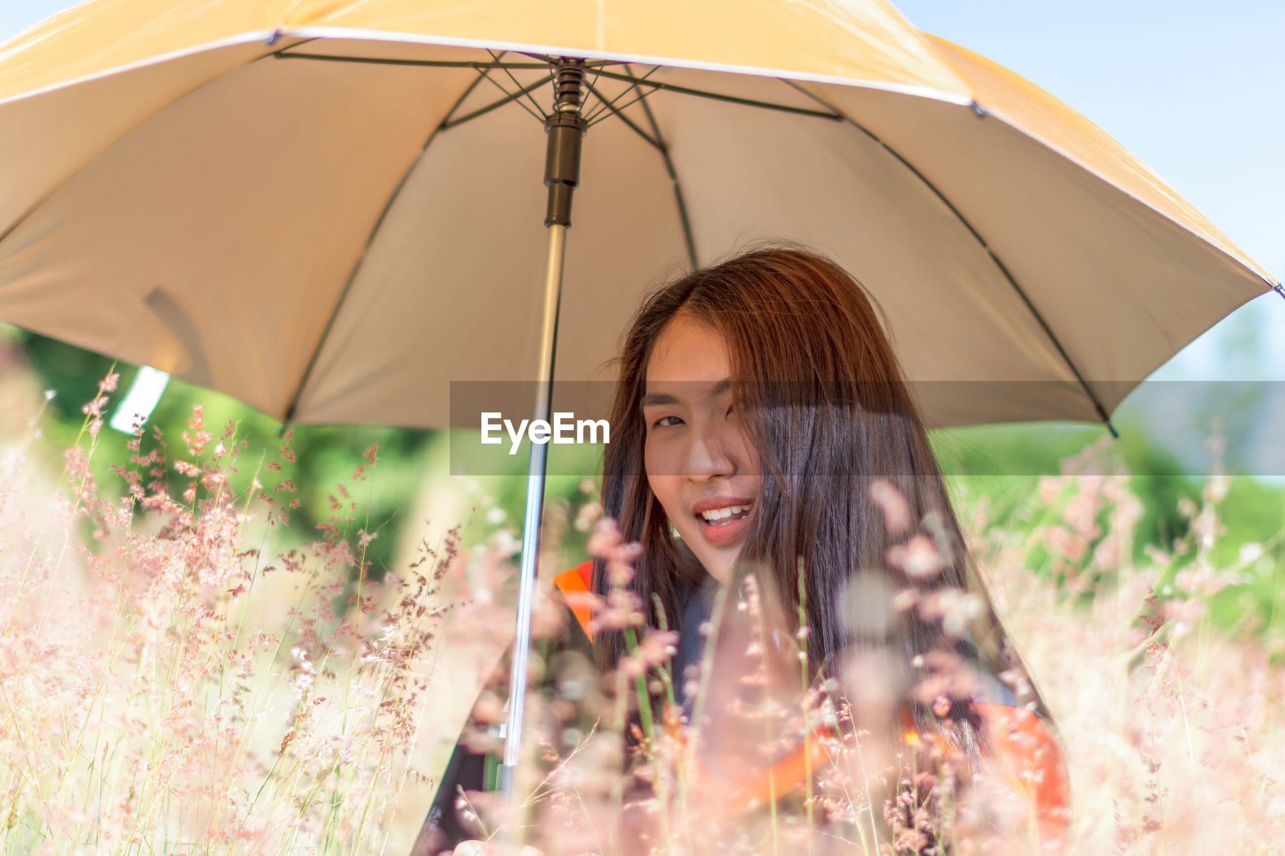 Portrait of smiling woman with umbrella on field