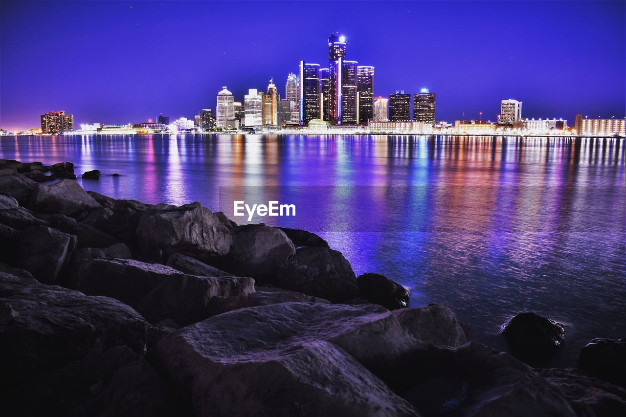 Illuminated Skyline By Detroit River At Night