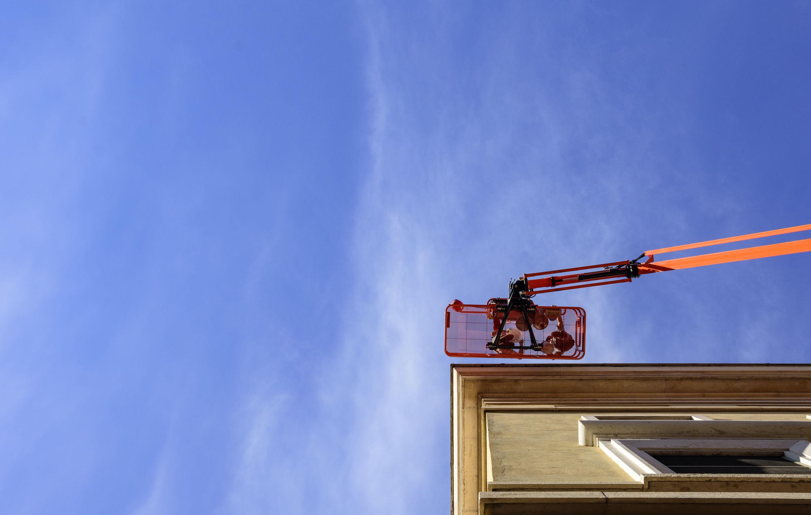 Low angle view of workers on hydraulic platform by building against blue sky