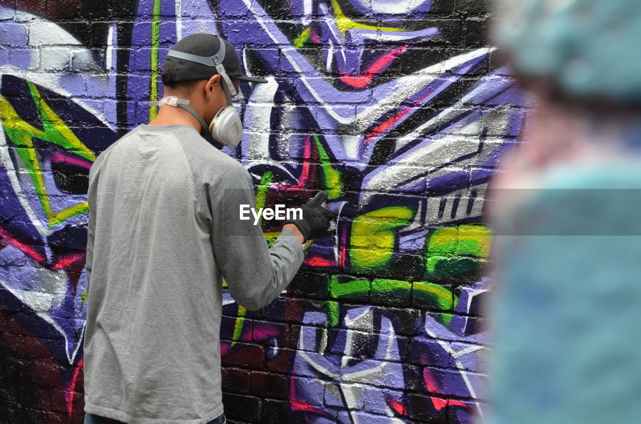 graffiti, multi colored, standing, casual clothing, one person, real people, young adult, lifestyles, skill, spraying, aerosol can, men, day, outdoors, one man only, adult, only men, people, adults only