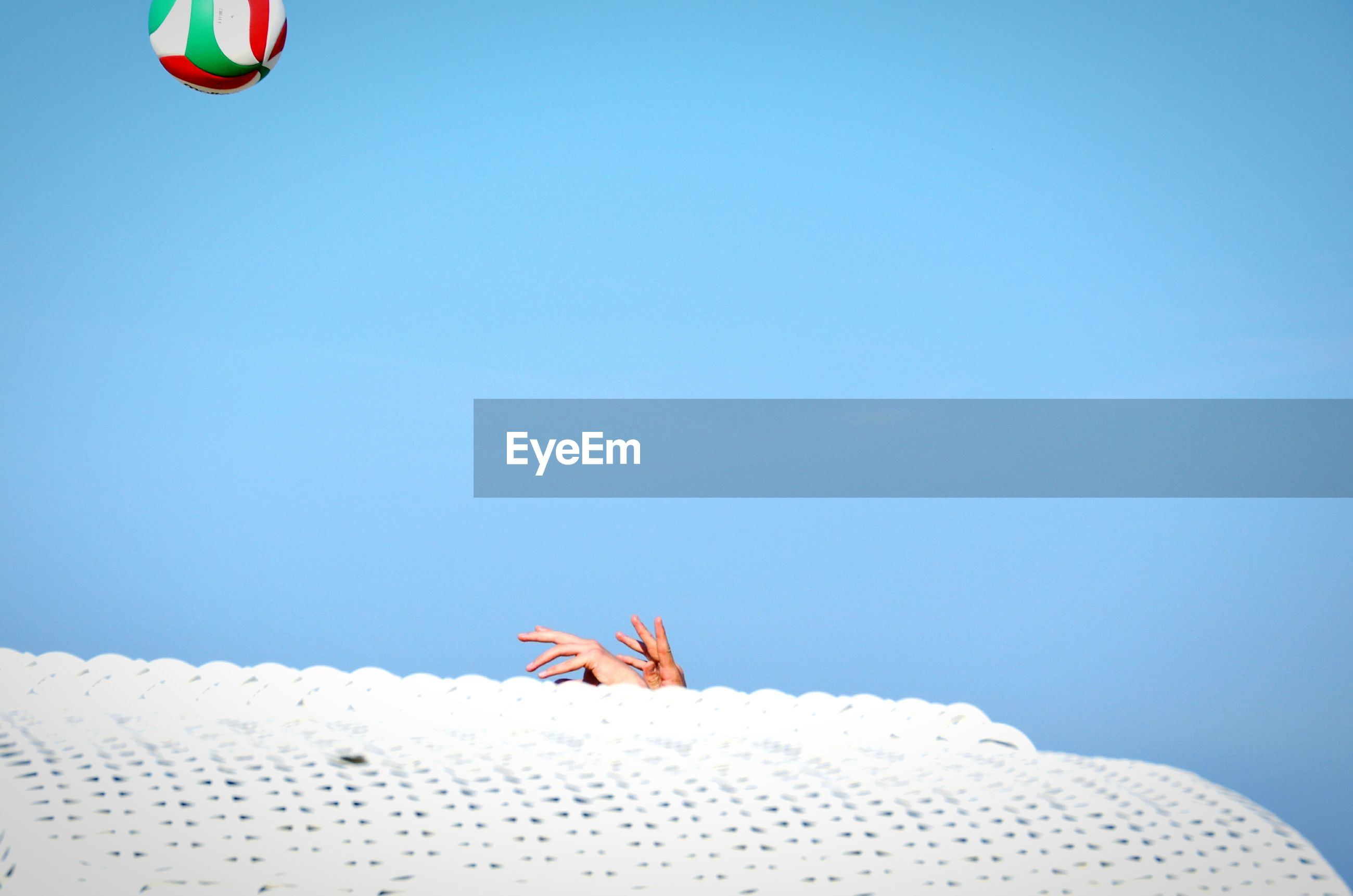 Hands reaching towards volleyball through ceiling against clear blue sky