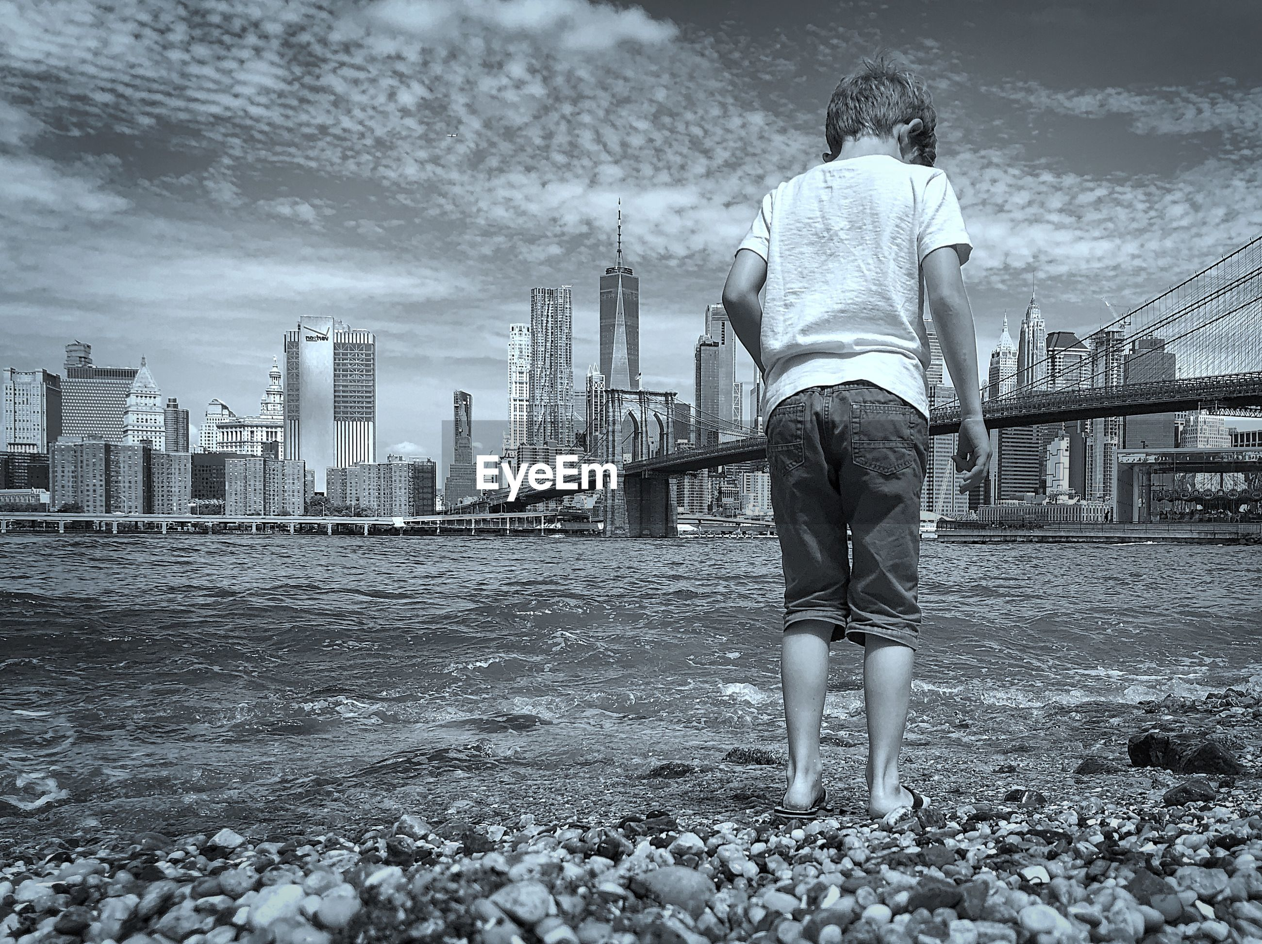 Rear view of boy standing at beach against cityscape