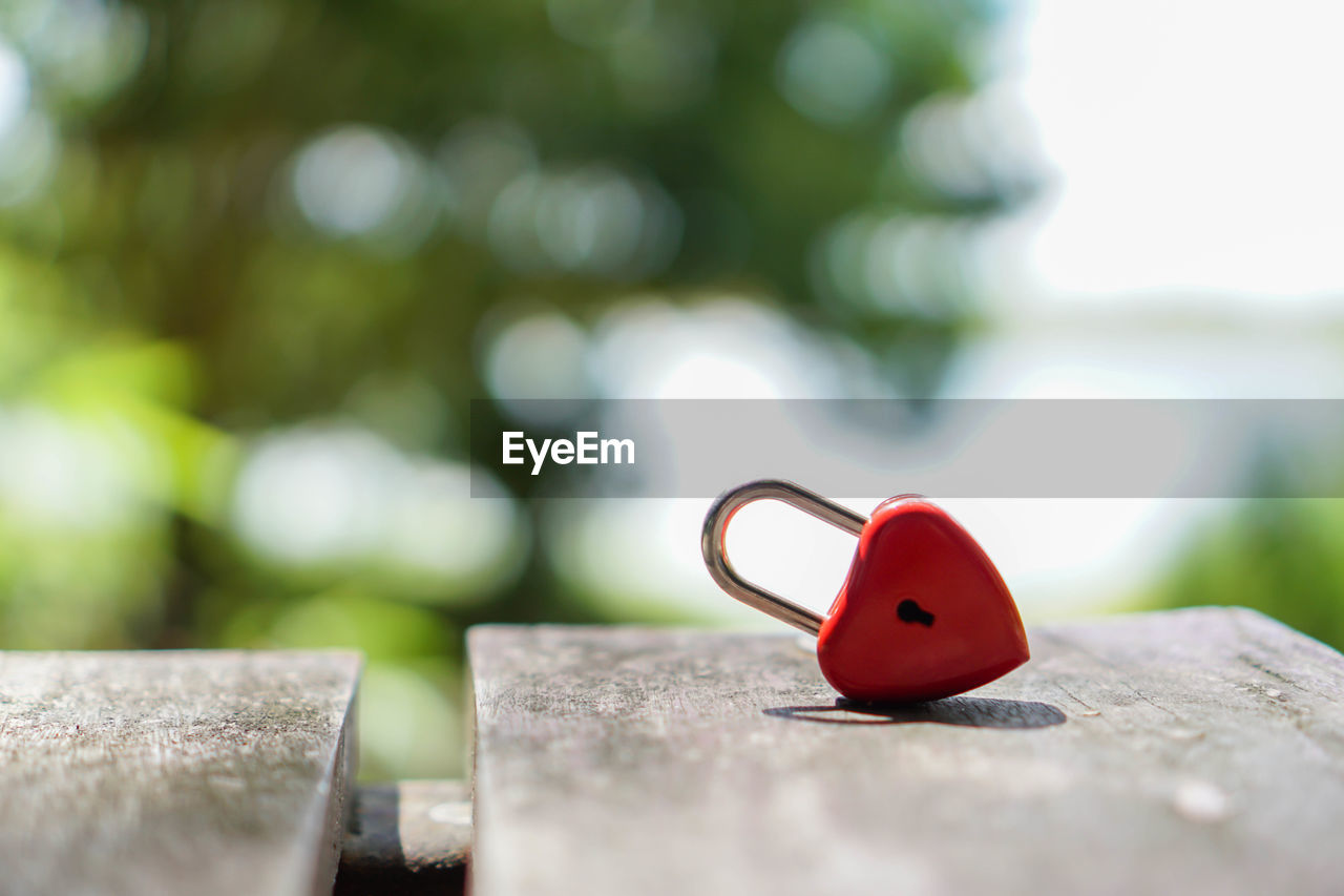 selective focus, close-up, wood - material, no people, day, red, focus on foreground, metal, solid, heart shape, outdoors, love, positive emotion, nature, still life, security, emotion, green color, protection, shape, silver colored