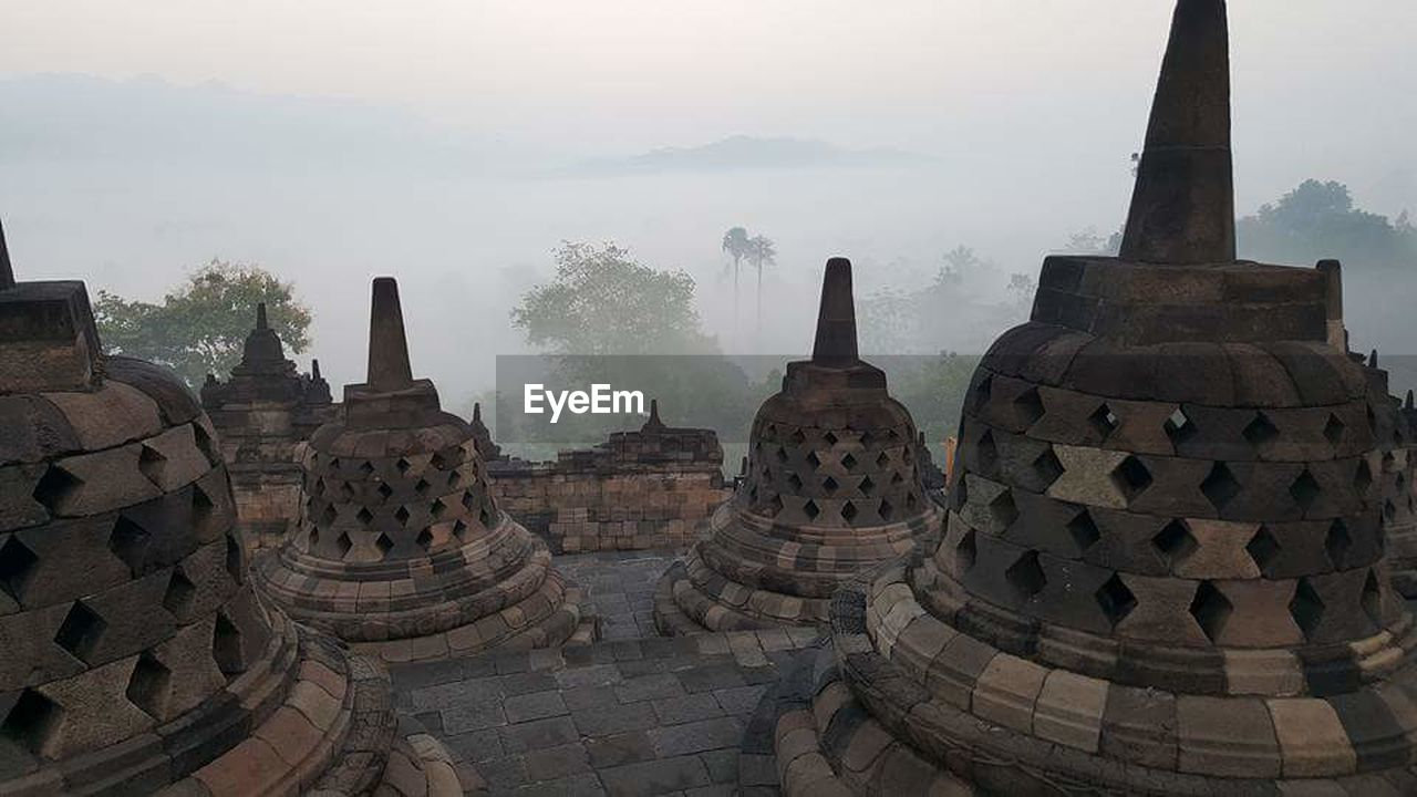 travel destinations, fog, architecture, spirituality, place of worship, religion, history, travel, tourism, built structure, monument, ancient, ancient civilization, no people, nature, tree, sky, day, building exterior, outdoors