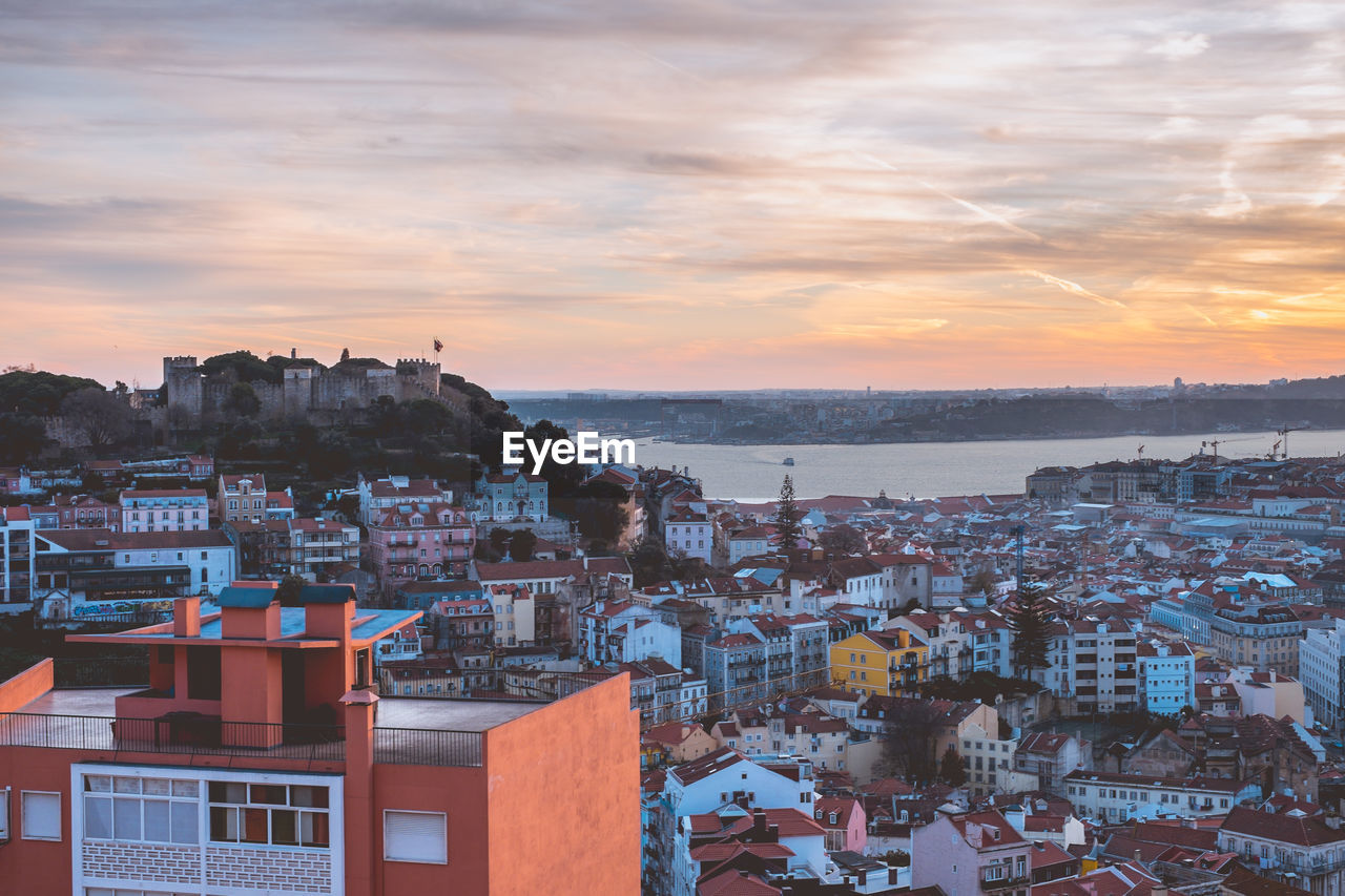 architecture, built structure, building exterior, sky, city, building, residential district, sunset, cloud - sky, crowd, cityscape, crowded, high angle view, nature, town, water, orange color, outdoors, community, townscape, settlement, romantic sky