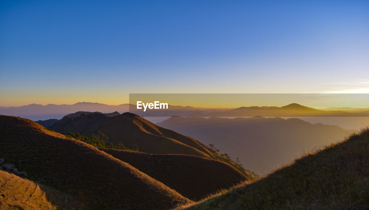 sky, mountain, scenics - nature, beauty in nature, sunset, tranquil scene, environment, tranquility, landscape, mountain range, non-urban scene, idyllic, nature, copy space, clear sky, no people, remote, orange color, outdoors, land