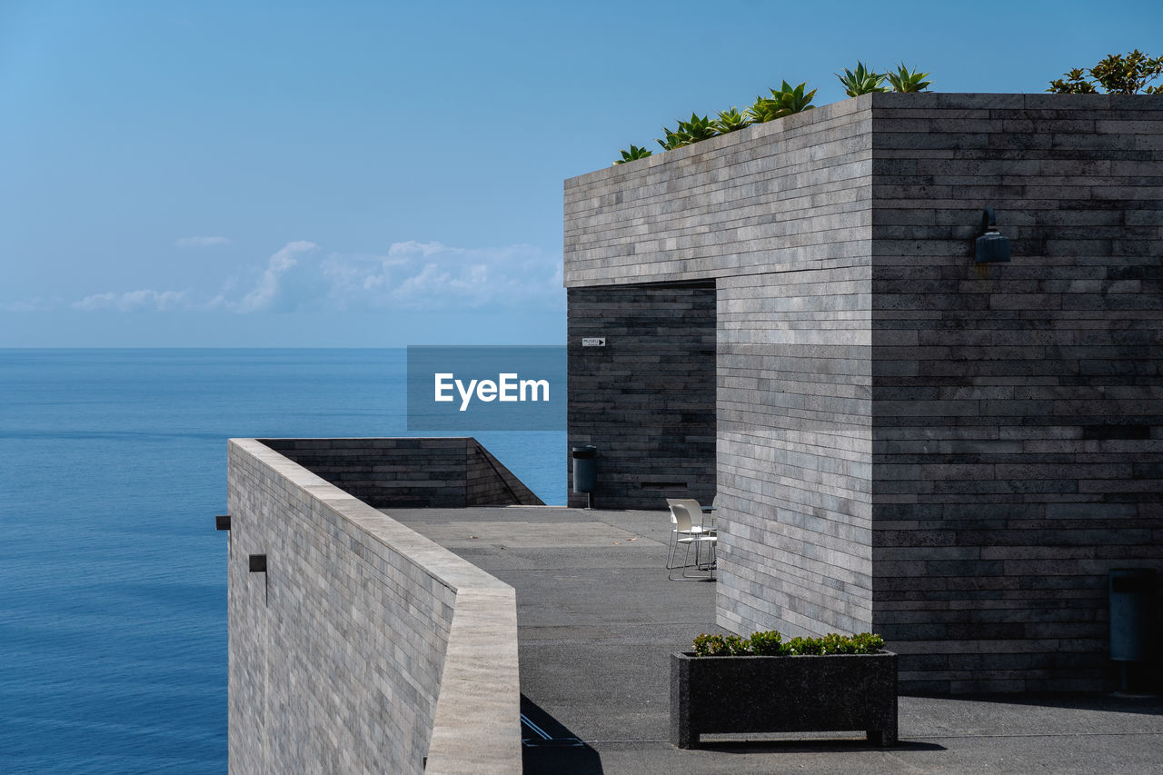 architecture, built structure, sky, sea, water, nature, building exterior, horizon, horizon over water, day, no people, wall, beauty in nature, sunlight, building, outdoors, plant, wall - building feature, potted plant