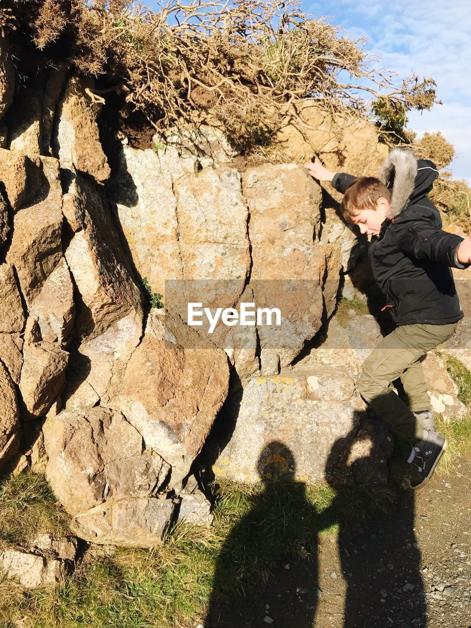 Full length of boy jumping by rock formation on sunny day