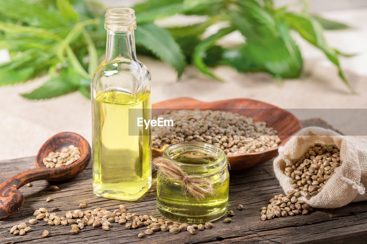food and drink, food, container, wellbeing, freshness, healthy eating, still life, nature, table, plant, oil, bottle, herb, no people, transparent, glass - material, close-up, olive oil, ingredient, wood - material