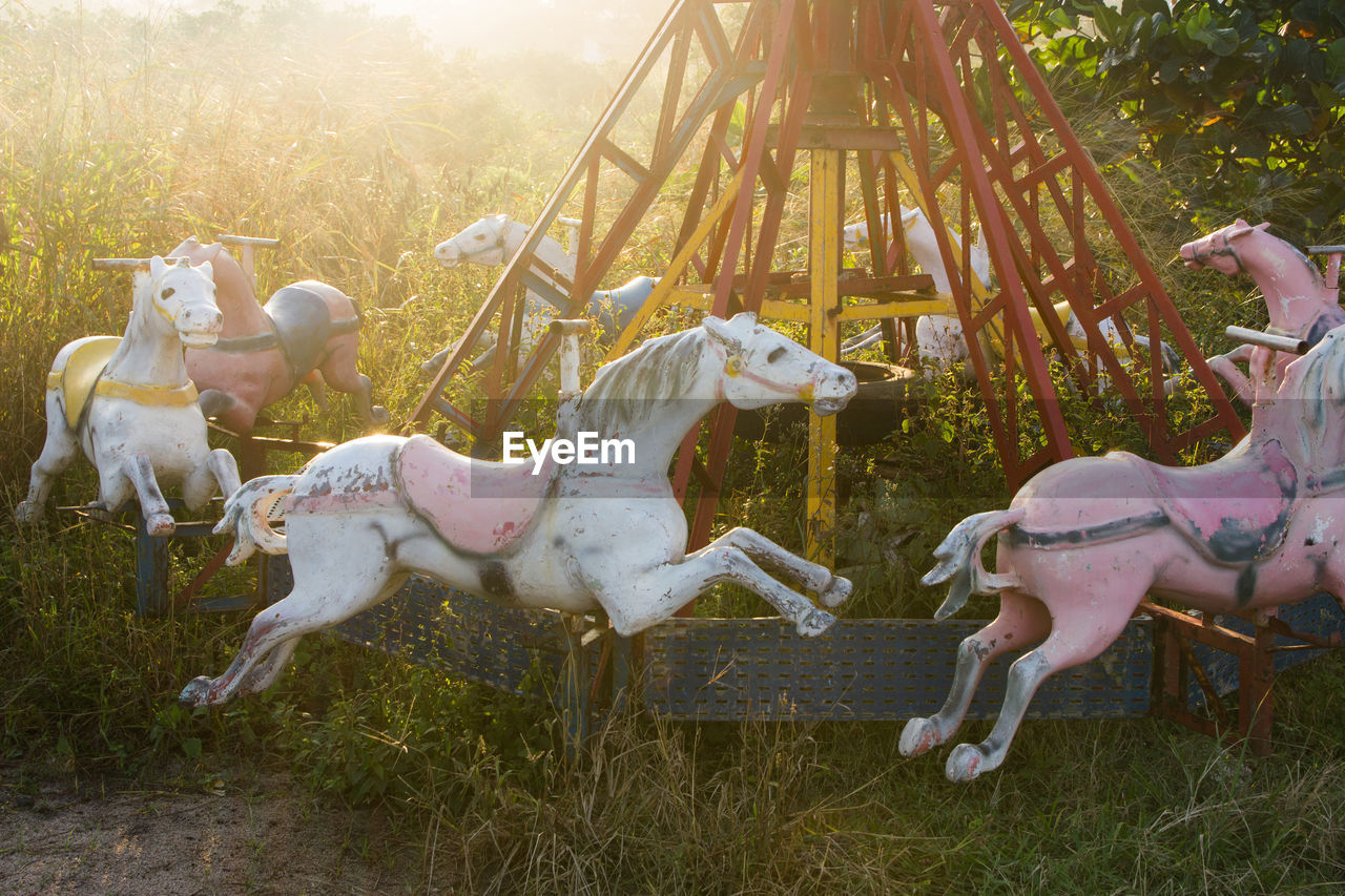 outdoors, amusement park, tree, day, carousel horses, carousel, togetherness, two people, full length, grass, animal themes, nature