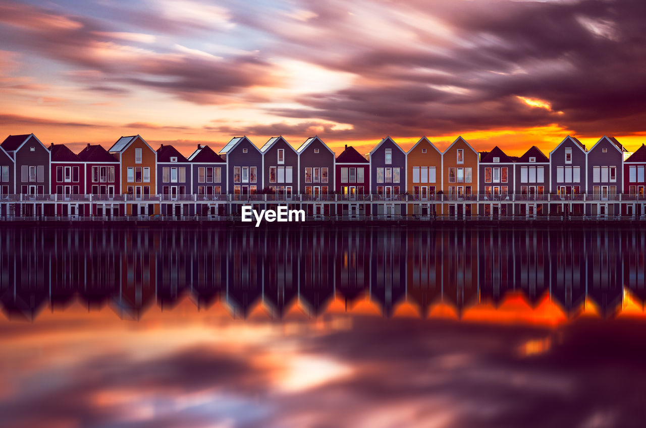 Reflection Of Houses In River Against Cloudy Sky During Sunset