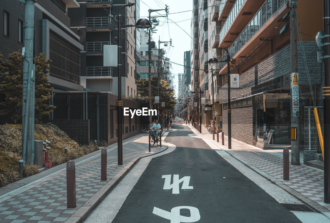 architecture, building exterior, city, built structure, sign, transportation, street, road, building, symbol, day, communication, bicycle, direction, road marking, text, incidental people, marking, real people, guidance, riding, outdoors