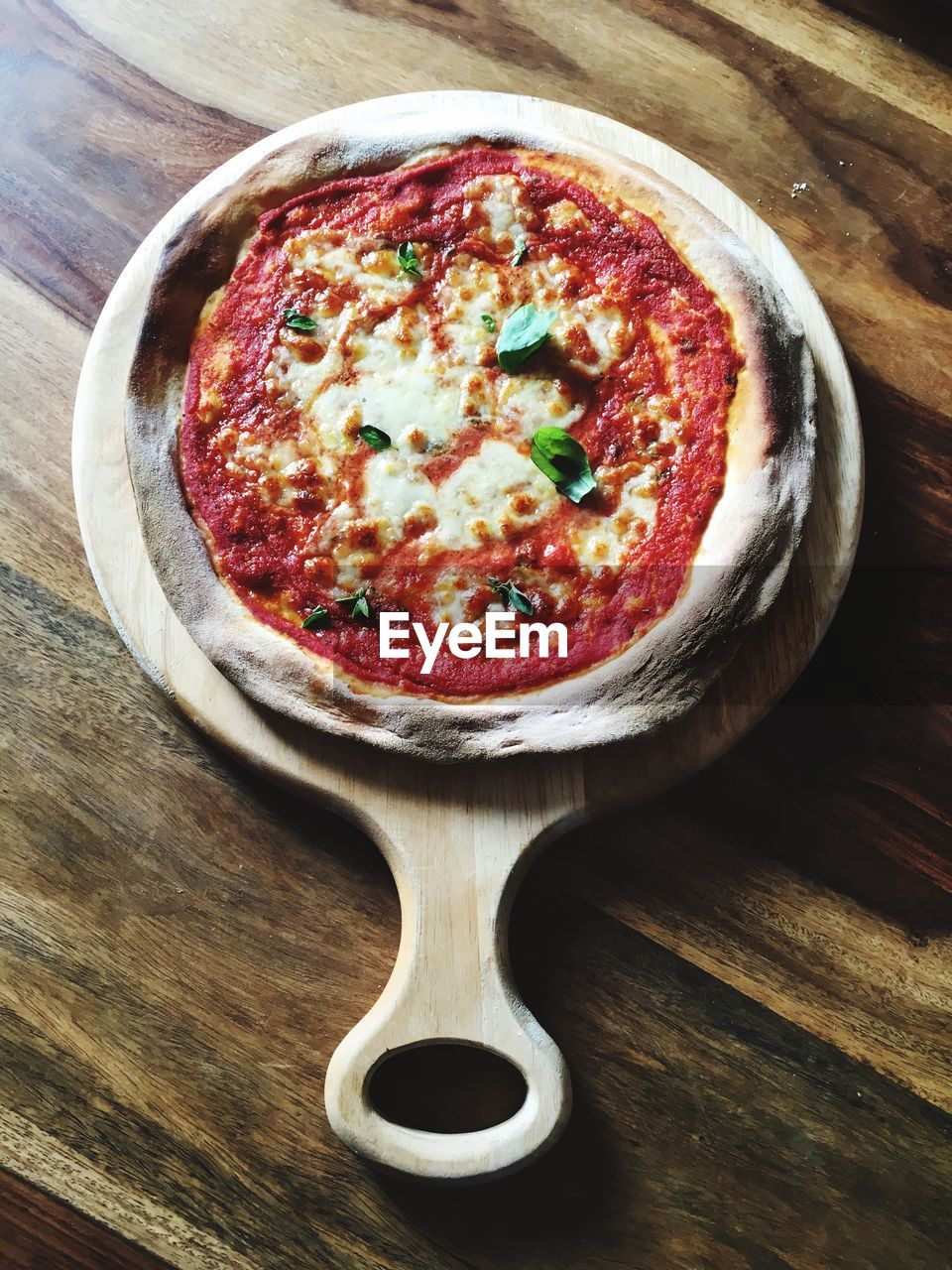 High angle view of fresh pizza on cutting board served on table