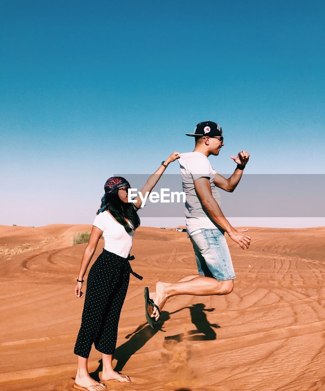desert, sunglasses, sand, young women, arid climate, young adult, sunny, standing, two people, fashion model, clear sky, day, outdoors, sunlight, nature, landscape, blue, sand dune, full length, togetherness, sky, women, friendship, beauty in nature, adult, people
