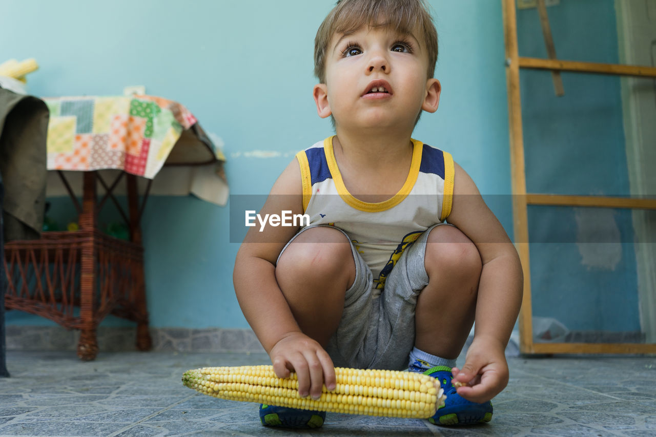 Full Length Of Cute Boy With Corn Crouching At Home