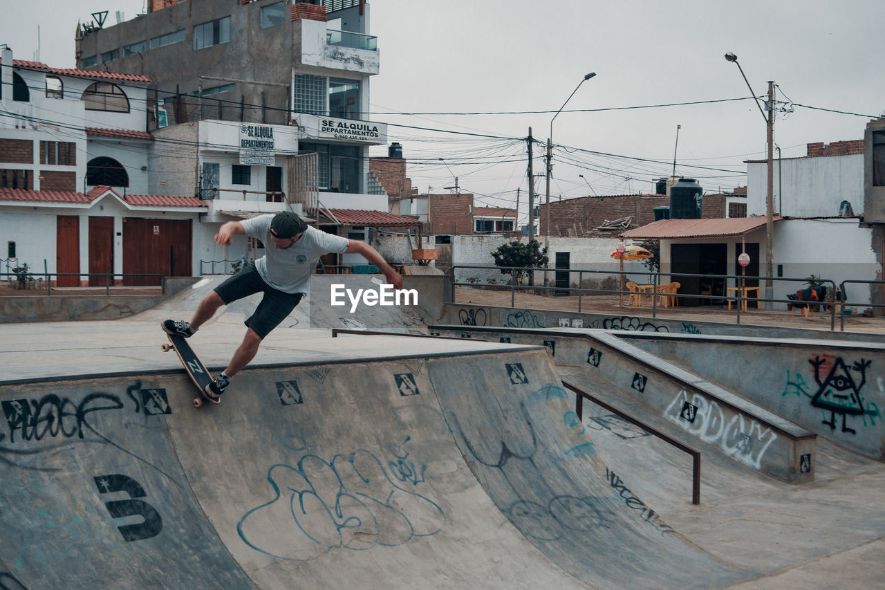 building exterior, full length, architecture, real people, built structure, leisure activity, men, city, sport, one person, lifestyles, skateboard park, mid-air, balance, stunt, day, sky, skill, city life, outdoors