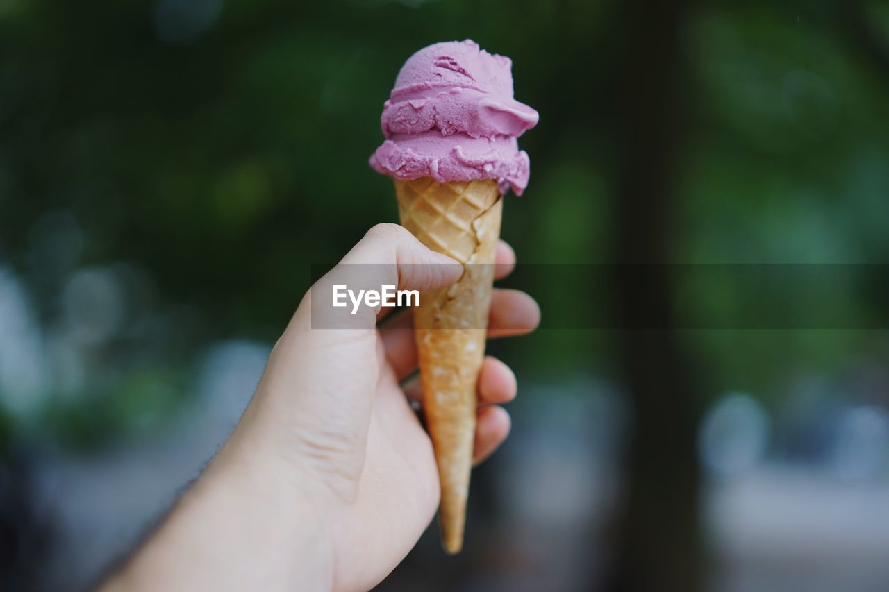 Cropped hand holding ice cream cone