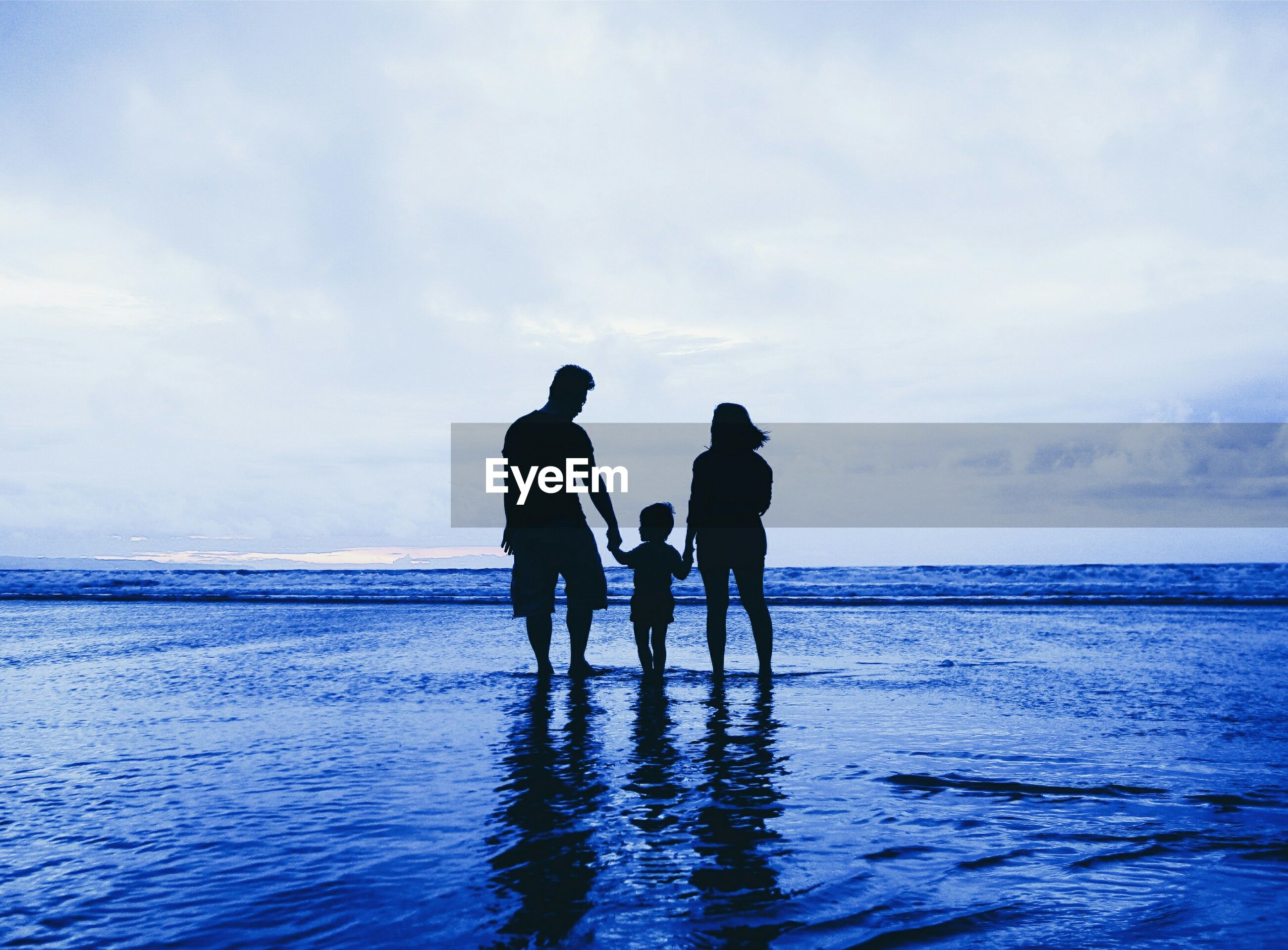 Silhouette family standing on shore at beach against cloudy sky
