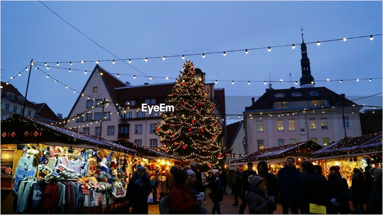 built structure, celebration, architecture, building exterior, large group of people, christmas, real people, christmas decoration, illuminated, tradition, night, sky, christmas lights, clear sky, celebration event, men, traditional festival, outdoors, women, crowd, lifestyles, city, people