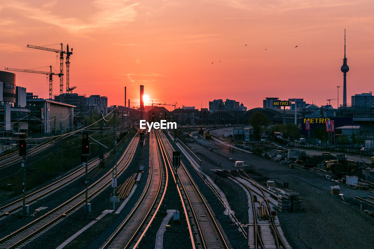 architecture, sunset, building exterior, track, rail transportation, built structure, railroad track, transportation, sky, city, orange color, tower, mode of transportation, travel, public transportation, high angle view, nature, no people, train, outdoors, spire, cityscape, shunting yard