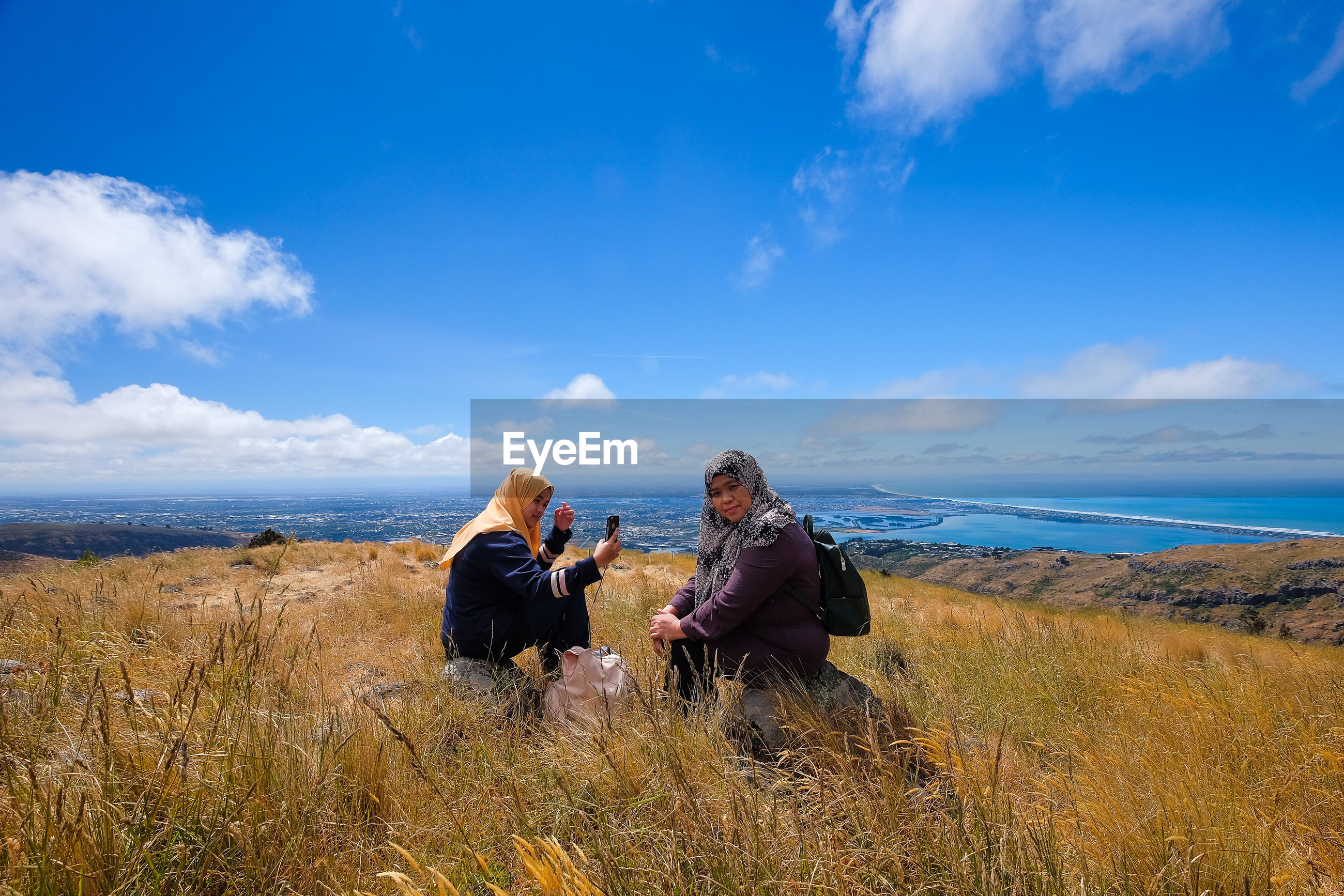 Family sitting on mountain against blue sky during sunny day