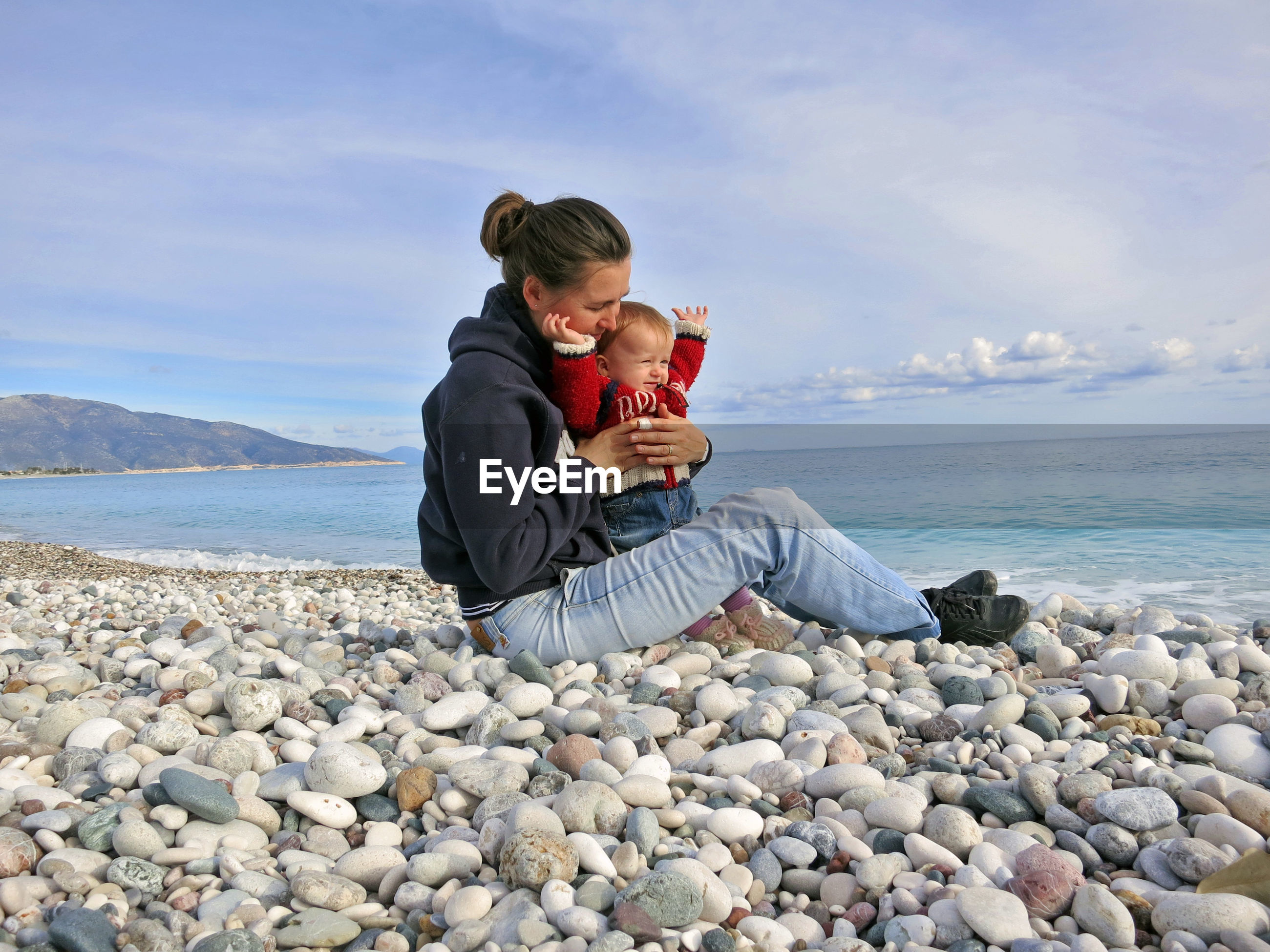 Woman with sitting daughter on pebbles at beach against sky