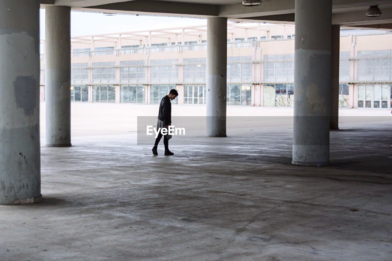 Men Walking In Empty Parking Lot