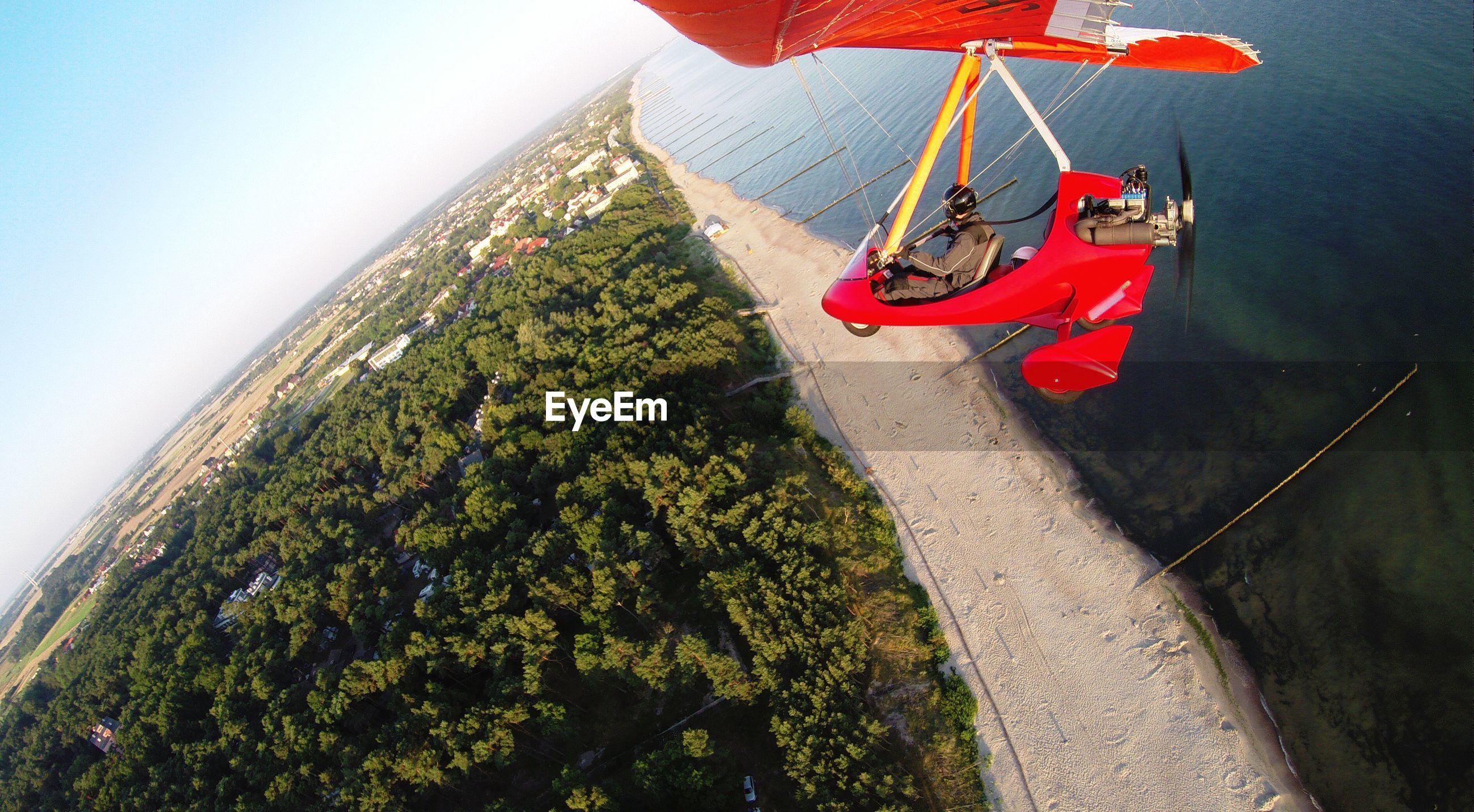 High angle view of man flying ultralight over sea