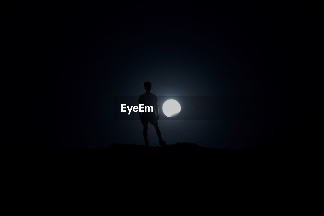 LOW ANGLE VIEW OF SILHOUETTE MAN STANDING AGAINST MOON