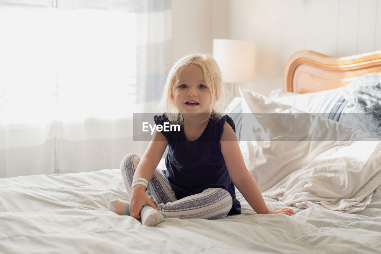 Full length portrait of girl sitting on bed at home