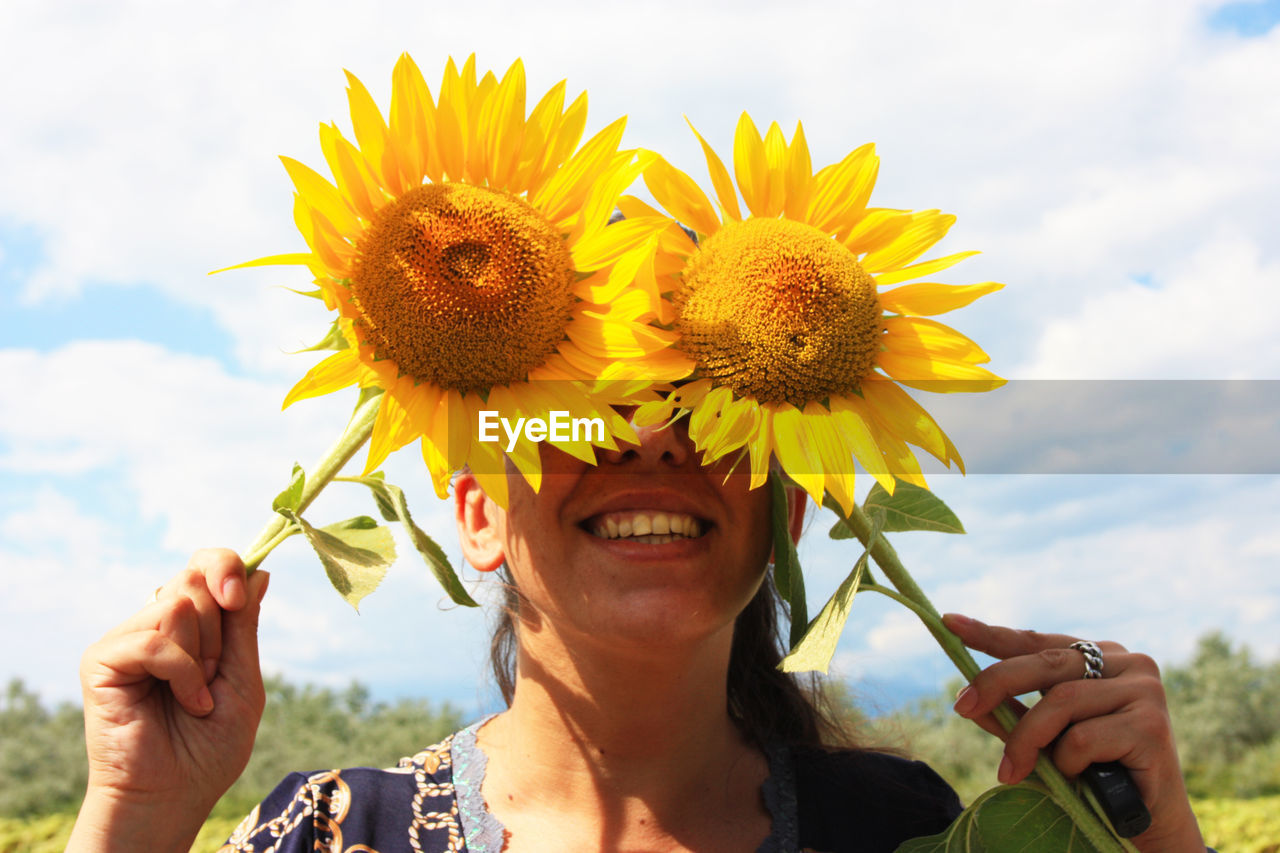 Happy nice woman hides behind yellow blooming sunflowers in summer