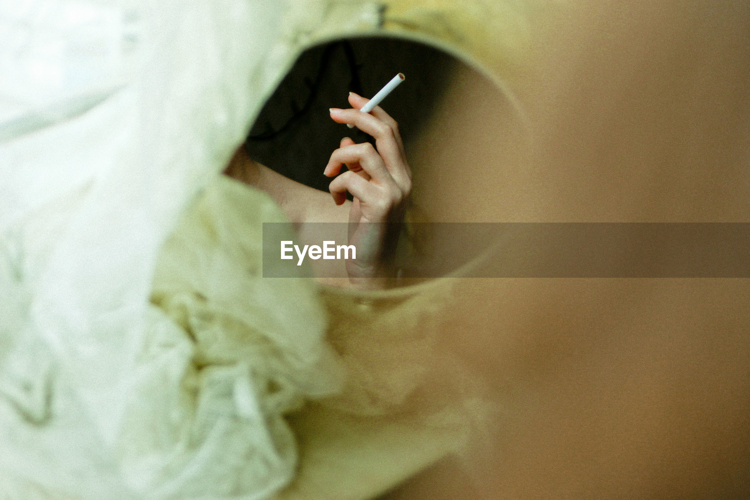 Reflection of woman holding cigarette