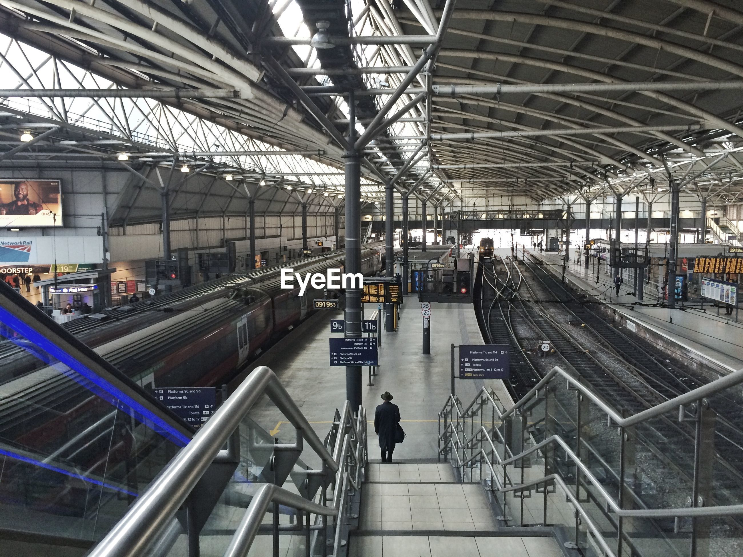 indoors, railroad track, architecture, built structure, rail transportation, railroad station, railroad station platform, ceiling, public transportation, transportation, metal, incidental people, transportation building - type of building, men, travel, day, high angle view, train - vehicle, railing