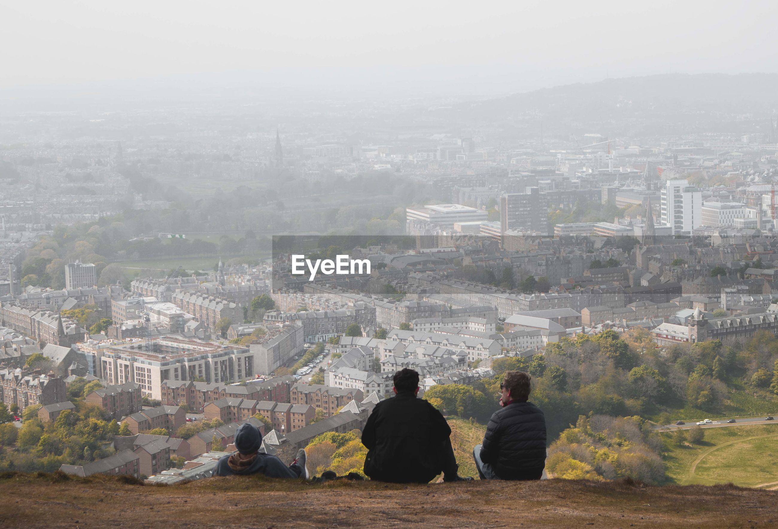 REAR VIEW OF PEOPLE LOOKING AT CITYSCAPE