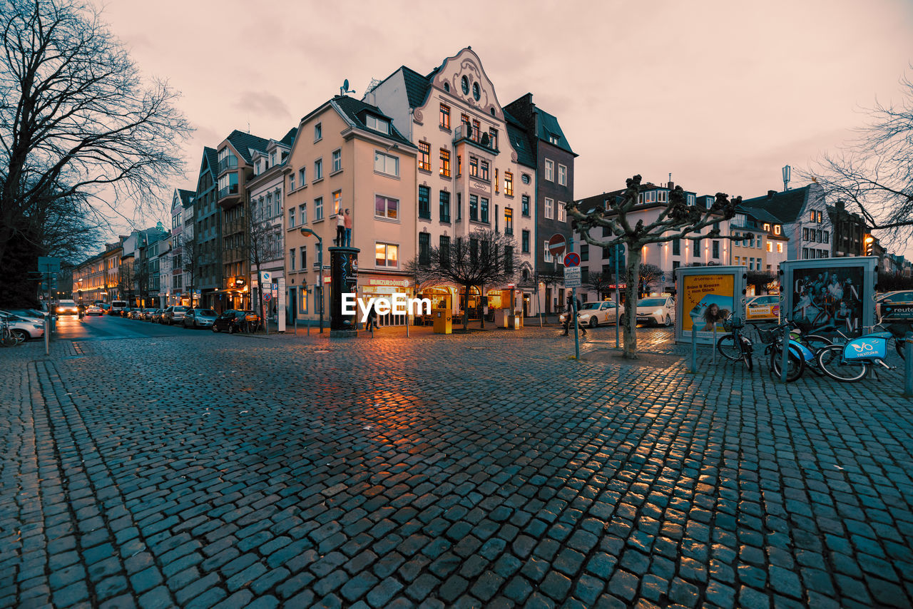 building exterior, architecture, built structure, city, street, building, sky, residential district, cobblestone, illuminated, transportation, nature, dusk, mode of transportation, incidental people, tree, outdoors, town, footpath, paving stone