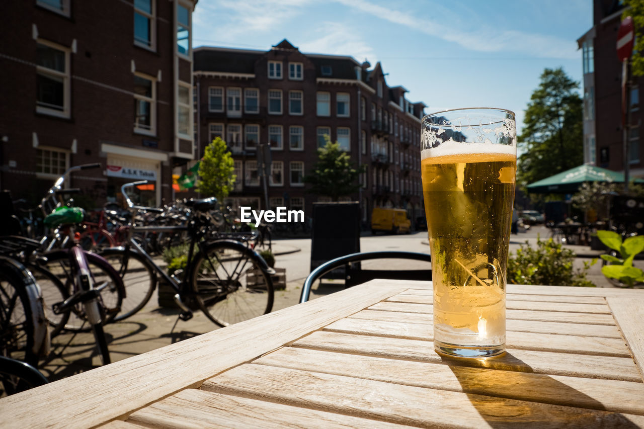 food and drink, building exterior, architecture, built structure, drink, refreshment, glass, drinking glass, beer, table, transportation, day, sunlight, bicycle, no people, beer - alcohol, nature, city, shadow, household equipment, outdoors, beer glass