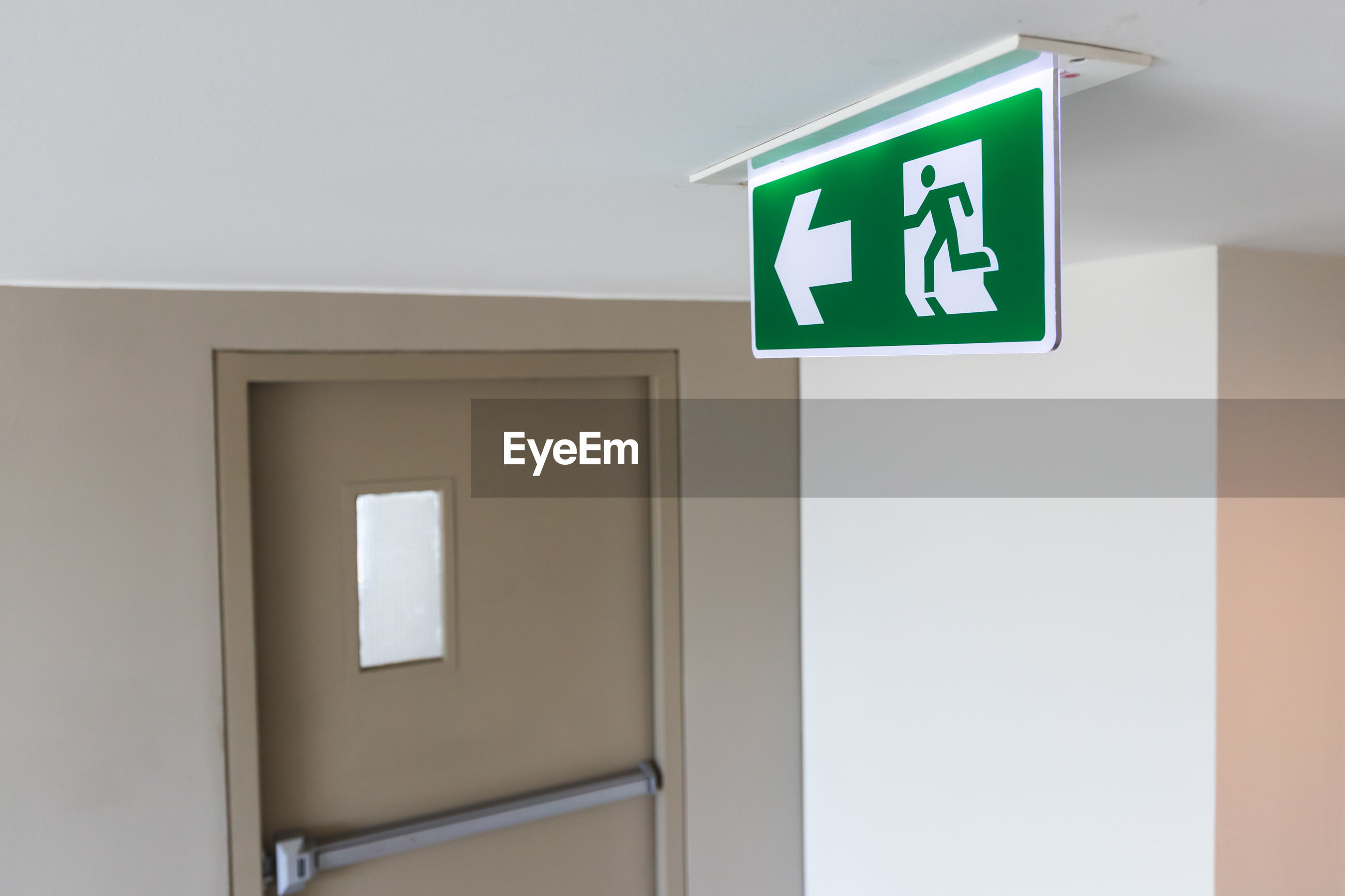 Close up view of the fire exit sign and the fire exit door that is closed in the building