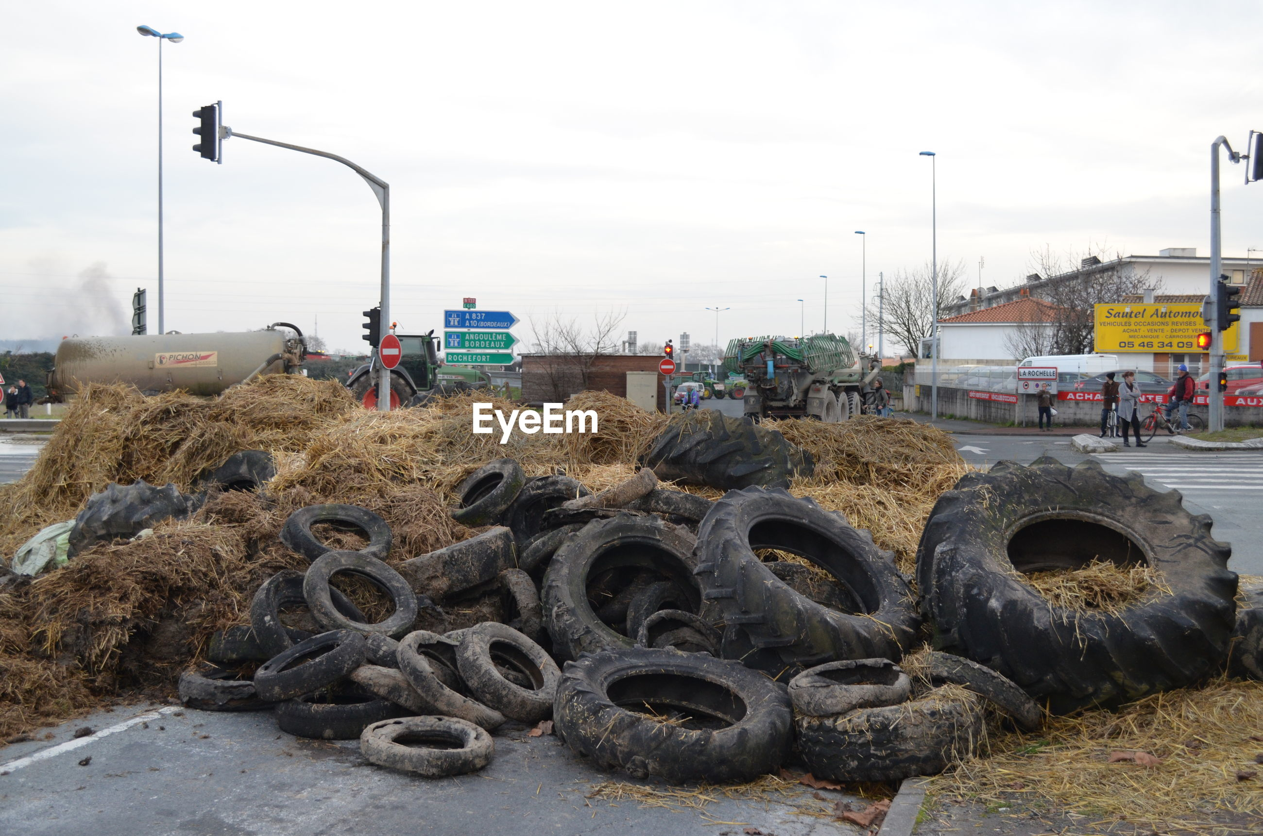 Obsolete tires at junkyard by road against sky